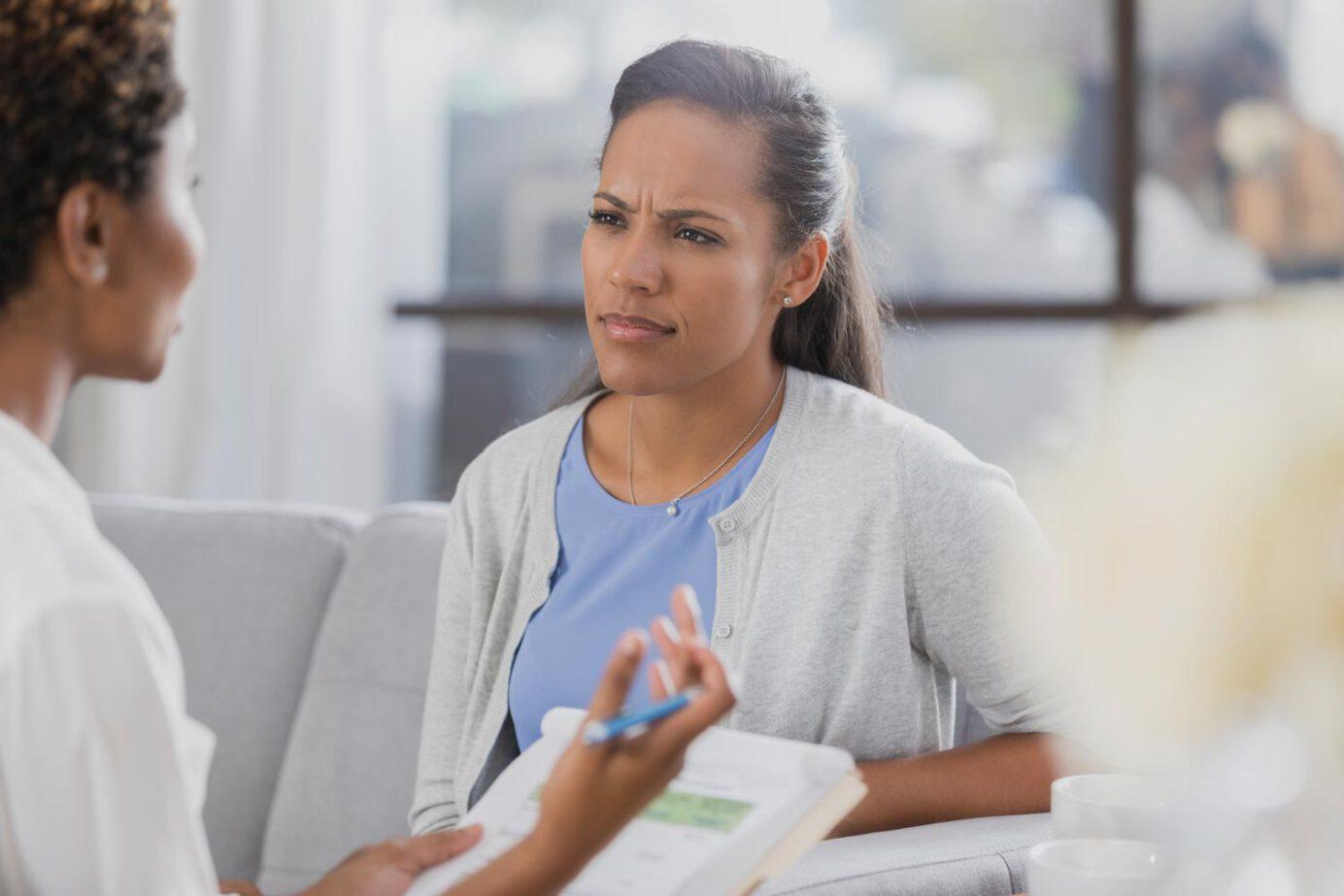 Frau mit ein wenig verständnisloser Miene hört ihrer Gesprächspartnerin zu